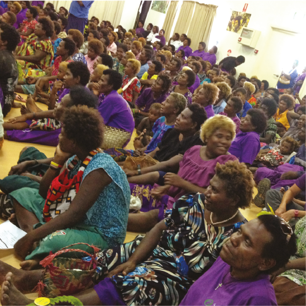Large group of women sitting on floor during meeting