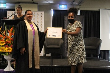 Amelia Raka being presented with her certificate